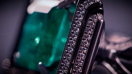 Close up of breathtaking platinum cufflinks with diamonds and emeralds. Video. Beautiful jewelry for man isolated on dark background under the spotlight.