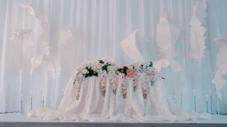 White wedding presidium decorated with flowers against white walls with feathers. Video. Concept of celebration and love, a table for newlyweds at the hall.