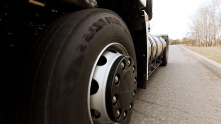 Freight semi truck driving and turning fast on empty highway. Scene. Close up of rotating car wheel on the background of a road and trees.
