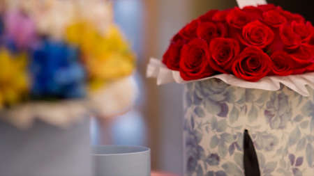 Creative decoration with bouquets of natural flowers in beautiful boxes. Video. Close up of colorful flowers as decor elements, concept of celebration.