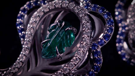 Brooch in with stones on a black rotating stand. Video. Close up of jewelry made of white gold, diamonds and emeralds on black background.