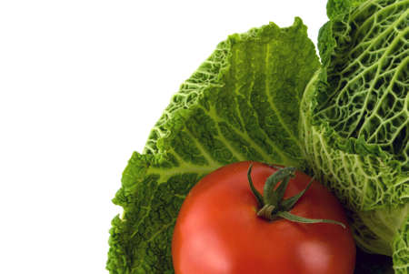 Green cabbage with a red juicy tomato on a white background photo