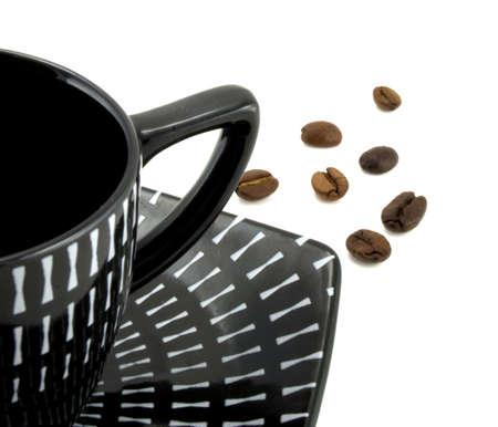 黒いカップと白い背景の上のコーヒー穀物