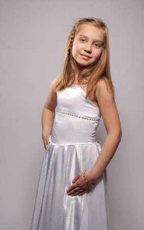 Smiling girl blonde in a white dress Stock Photo