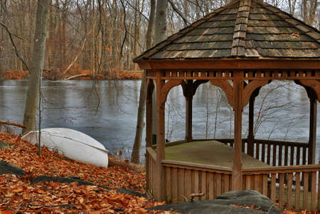 The wooden arbor on the bank of the stood lake photo