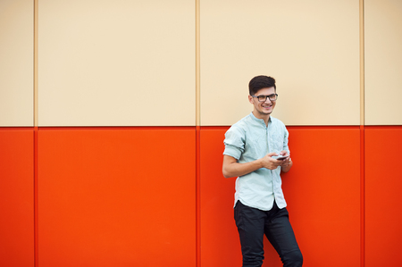 Portrait of handsome man using his mobile in the street on orange background.