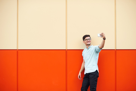 Casual man taking a selfie in the street on the big orange wall. Foto de archivo - 124959854