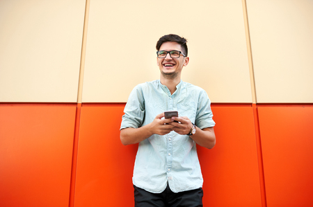 Happy man with glasses standing and using smartphone over orange background. Imagens
