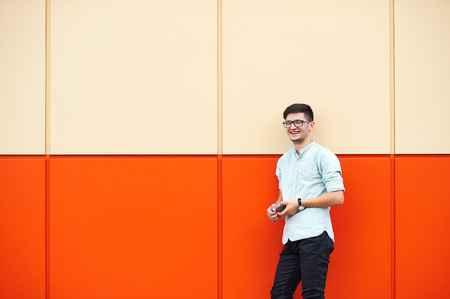Young confident hipster man in glasses posing on the orange background. Outdoor. Cute man wearing a blue shirt. Man keeps phone in hands and looking forward Foto de archivo - 124959861