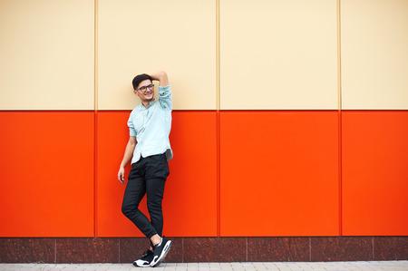 Full-length shot of smiley man standing against huge orange wall looking on the left Foto de archivo - 124959886