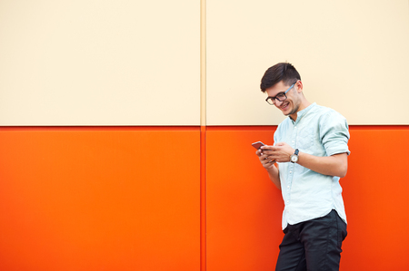 Young attractive man smilling and using mobile phone in the street.