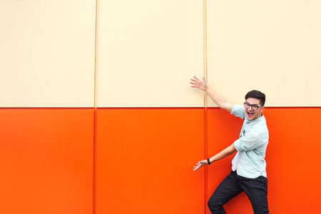 Handsome trendy man in glasses pointing away with both hands and laughing on orange background Foto de archivo - 124959895