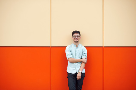 Close up portrait of a young boy in blue tshirt, against the backdrop of an orange wall