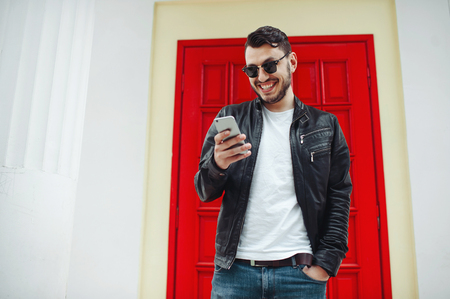 Image of handsome male in black leather jacket reading a messeage from a cellphone and smiling over a red door Banque d'images - 119659725