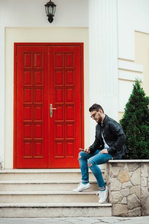 Handsome and confident male using a smartphone outdoor. Stylish man in sunglasses and black leather jacket sitting on stairs. Banque d'images - 119659750