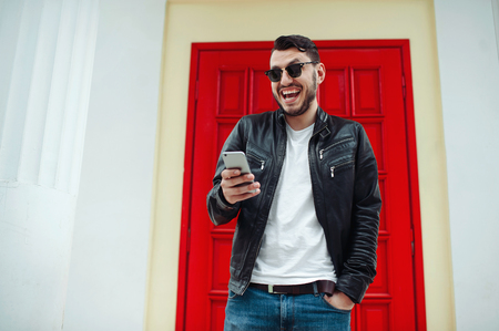 Image of handsome male in black leather jacket reading a messeage from a cellphone and smiling over a red door Banque d'images - 119659751