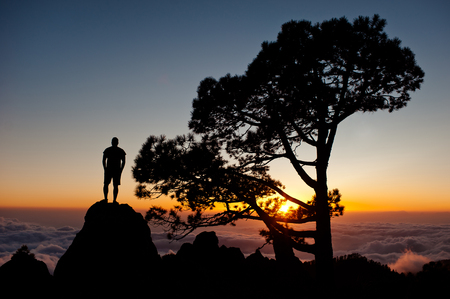 Sportsman with hands in pockets stand on the rock peak and watching the sunset. Silhouette of man. Hiker deep think with hands in pocket. Stock Photo
