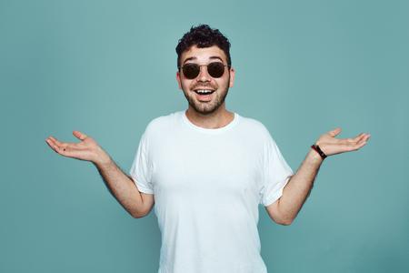 I dont now. Bearded man in sunglasses and white t sirt is gesturing unknown sign isolated over blue background. Young hipster with confuce face expression