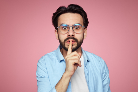 Fashionable hipster guy demands keeps silence, shows hush gesture, looks with stunned expression at camera, afraids of gossiping, isolated over pink background. Mute man
