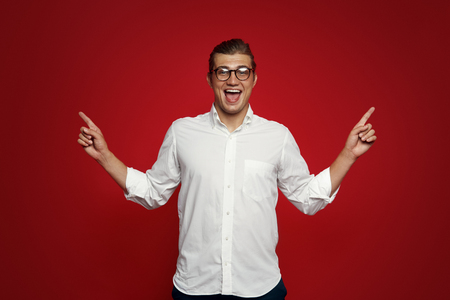 Joyful handsome man indicates with both fore fingers up, has friendly smile, shows blank space against red background. People, advertisement concept.
