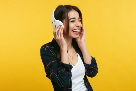 Overjoyed young girl enjoy sound of music, keeps hands on headphones, closes eyes from pleasure, listens song and feels glad, expresses happiness. Cute female wearing stylish outfit above yellow wall Фото со стока - 120657932