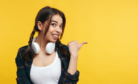 Amused pleasant looking positive girl points on right, wearing casual shirt and white headphones, shows free space against yellow background, suggests going there, has friendly look at camera. Stock fotó