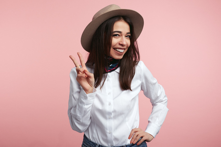 Pleased attractive woman shows v sign or peace gesture, wears white shirt and hat, isolated over rosy studio background. People, fashion, body language. Foto de archivo - 122003330