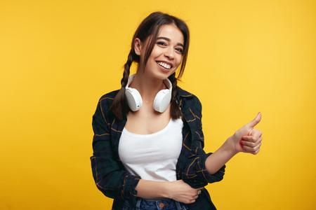 Retrato de adolescente feliz mantiene el pulgar levantado, de buen humor, muestra su acuerdo, posa sobre fondo amarillo. Chica joven con auriculares muestra como gesto, satisfecho con algo.