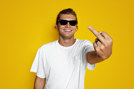 Indoor shot of young brutal man shows middle finger and smiles, shows his dislike or discontent with something, wears white t shirt, says Fuck you. Male hipster isolated on yellow background Foto de archivo - 122003334