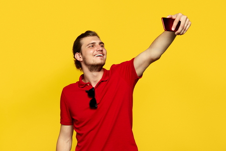 Portrait of happy handsome male with sunglasses posing isolated over yellow background, wearing red polo shirt, taking a selfie by phone. Foto de archivo - 122003335