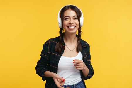 Portrait of happy teenager with white headphones, listens music and feels glad, smiling with broad smile showing her perfect teeth, standing isolated over yellow background Foto de archivo - 122003339