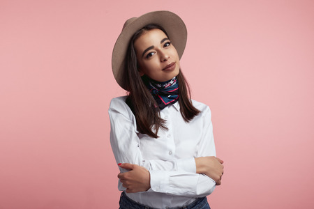 Horizontal shot of serious beautiful young female with crossed hands, dressed in elegant hat, white shirt and stylish scarf, shows her beauty against pink studio wall. People and lifestyle concept Foto de archivo - 122003354