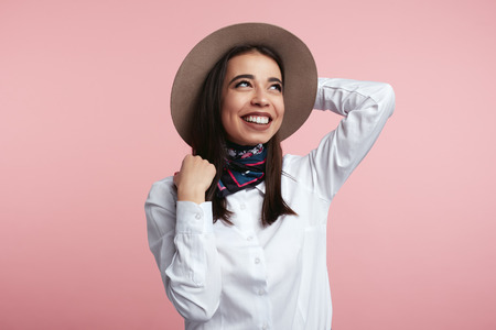 Fashionable brunette wearing white shirt and stylish scarf, holding her hat and looking away over pink studio background. Beauty, fashion concept. Foto de archivo - 122003355