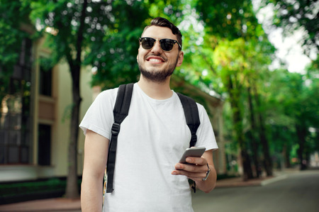 Fashionable bearded male using a smartphone outdoor. Handsome male with bagpack wearing white tshirt and sunglasses looking forward and smiling. Foto de archivo - 122003575