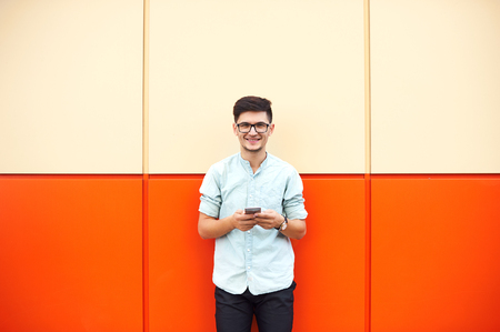 Happy man with glasses standing and using smartphone over orange background. Foto de archivo - 122003577