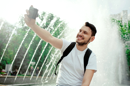 Perfect selfie. Cheerful man smiling into the camera while taking a selfie and showing peace gesture. Unshaven young boy wearing white tshirt and black bagpack outdoor. Foto de archivo - 122003580