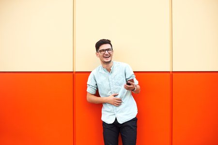 Happy attractive man with eyeglasses wearing stylish clothes, standing and using smartphone over orange background. Foto de archivo - 122003583