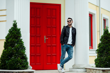 Handsome happy hipster young man smiling outside. Bearded boy with a beautiful smile wearing stylish leather jacket, jeans and sunglasses posing on background of red door. Foto de archivo - 122003584