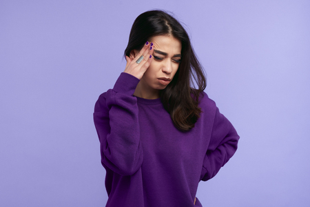 Portrait of fatigue 20s girl has terrible headache, keeps hand on temples, feels pain and frustration, closes eyes, has unhappy expression, isolated over violet background.