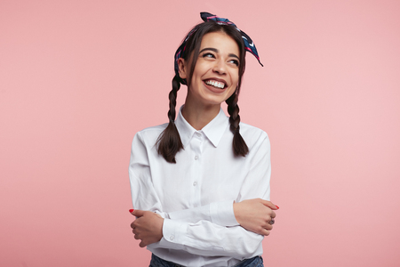 Portrait of pleasant looking woman with gentle smile on face, has healthy skin, wearing white shirt and headband, standing with crossed arms over pink background. Facial expressions concept. Foto de archivo - 122003587