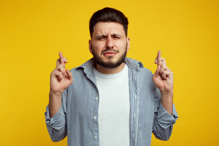Attractive bearded man closes eyes with big hope, crosses fingers as believes in something important, isolated over yellow wall Foto de archivo - 124961249
