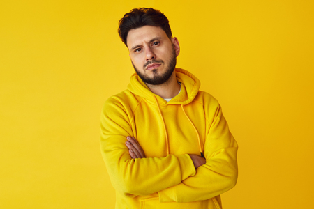 Young confident hipster male in yellow hoodie posing with arms crossed over yellow background