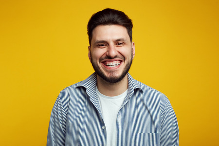 Attractive bearded young man laughing out loud, smiling broadly, showing his white straight teeth against yellow background Foto de archivo - 124961257
