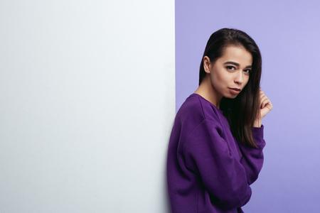 Pretty young girl, standing alongside empty white billboard wall isolated over purple background. Foto de archivo - 124961258