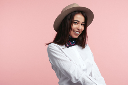 Young beautiful brunette girl wearing elegant hat, white shirt and stylish scarf, smiling and standing against pink wall Foto de archivo - 124961262