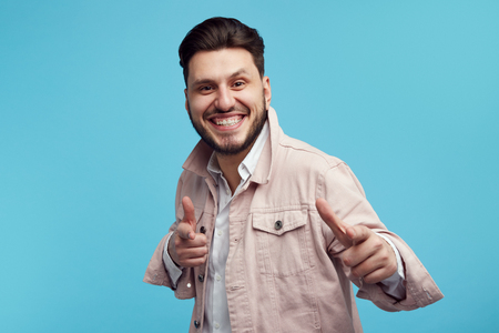 Handsome bearded man in pink jeans jacket and white shirt showing pointing gesture on blue background