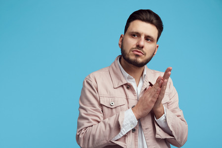 Portrait of young confident unshaven man keeps hands together, wearing pink jeans jacket and white shirt, stands against blue wall Foto de archivo - 124961477
