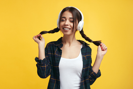Happy female teenager enjoy sound of music, holds her pony tails, closes eyes from pleasure, listens song and feels glad Foto de archivo - 124961486