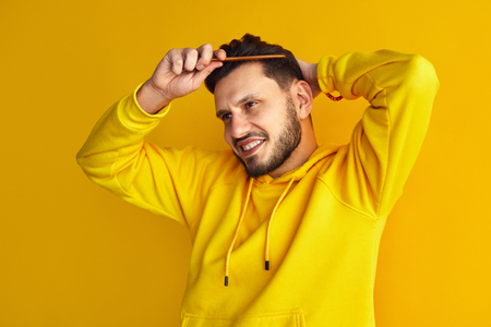 Attractive young boy, wearing yellow hoodie, smiling and combing his hair, makes hairstyle by himself, isolated over yellow wall Stock Photo