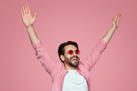 Cheerful bearded man, sharing happiness and raising his hands in the air, having fun and posing over pink background. Foto de archivo - 124961497